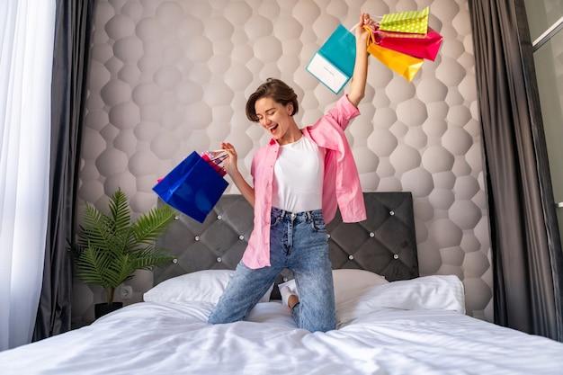 Femme assez heureuse s'amusant à sauter sur le lit à la maison avec des sacs à provisions colorés