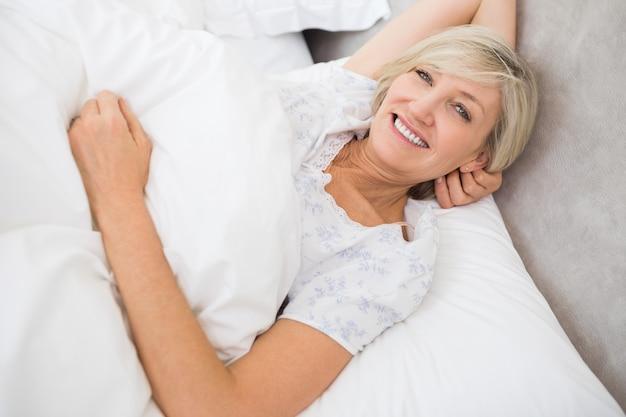 Femme assez mature au repos au lit