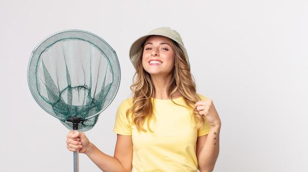 Femme assez mince à l'air arrogante, réussie, positive et fière portant un chapeau et tenant un filet de pêche