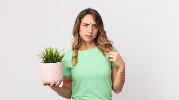 Femme assez mince à l'air arrogante, réussie, positive et fière et tenant une plante décorative