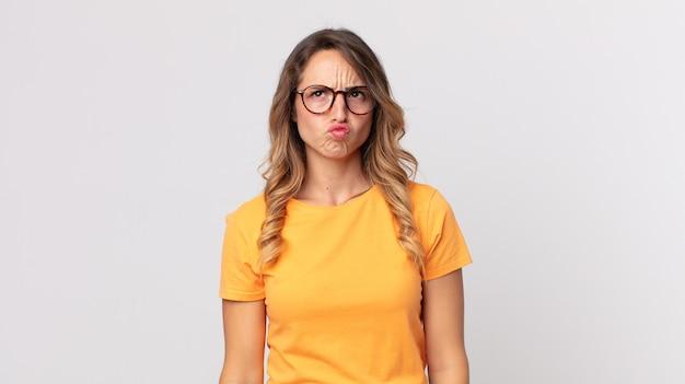 Femme assez mince à l'air maladroit et drôle avec une expression stupide qui louche, plaisantant et s'amusant