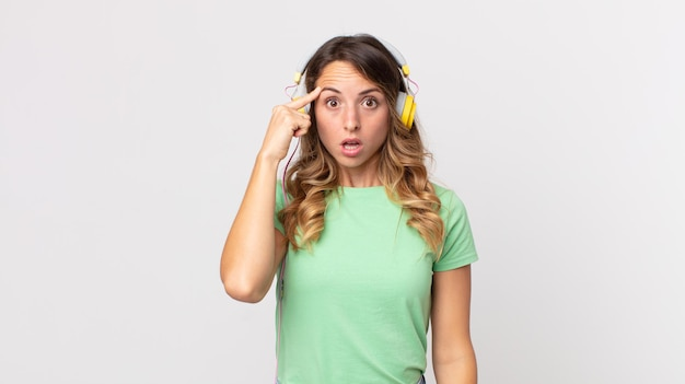 Femme assez mince ayant l'air surprise, réalisant une nouvelle pensée, idée ou concept écoutant de la musique avec des écouteurs