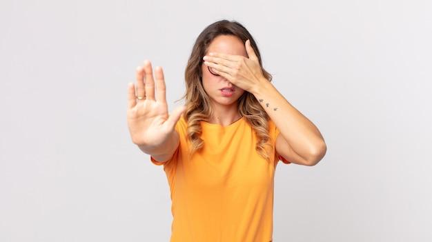 Femme assez mince couvrant le visage avec la main et mettant l'autre main devant pour arrêter l'appareil photo, refusant des photos ou des images