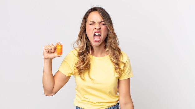 Femme assez mince criant agressivement, ayant l'air très en colère et tenant des piles