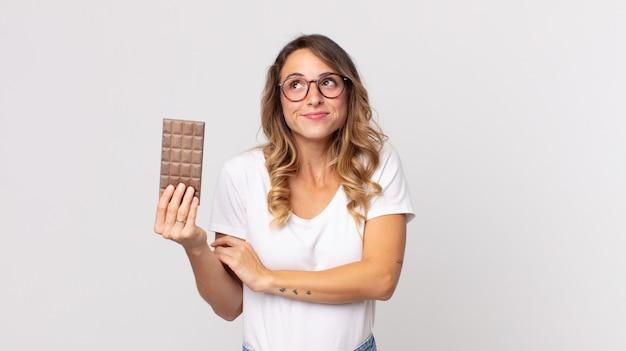 Femme assez mince haussant les épaules, se sentant confuse et incertaine et tenant une barre de chocolat