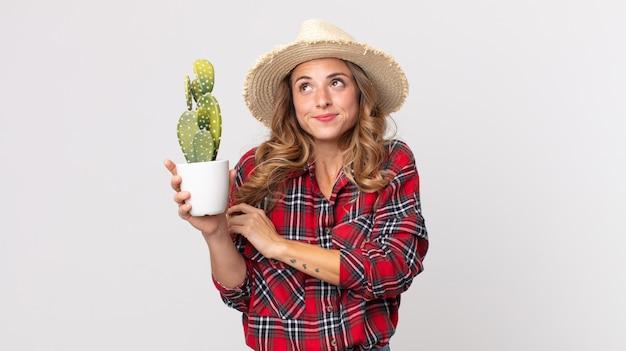 Femme assez mince haussant les épaules, se sentant confuse et incertaine tenant un cactus. concept d'agriculteur
