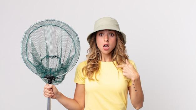 Femme assez mince qui a l'air choquée et surprise avec la bouche grande ouverte, pointant vers l'autoportant un chapeau et tenant un filet de pêche