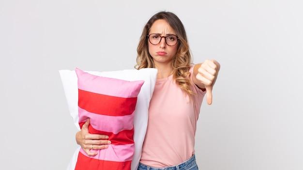 Femme assez mince se sentant croisée, montrant les pouces vers le bas en pyjama et tenant un oreiller
