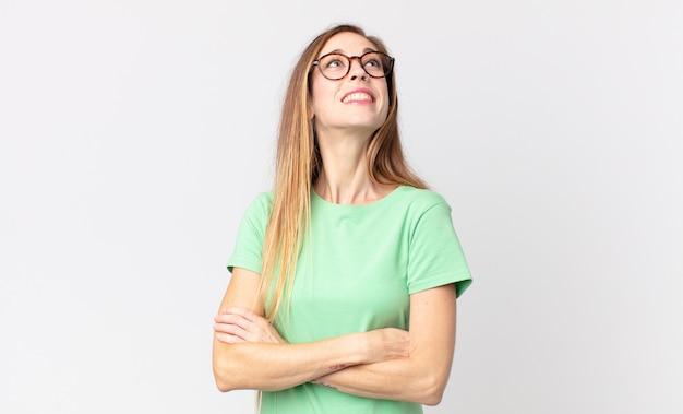 Femme assez mince se sentant heureuse, fière et pleine d'espoir, se demandant ou pensant, levant les yeux pour copier l'espace avec les bras croisés