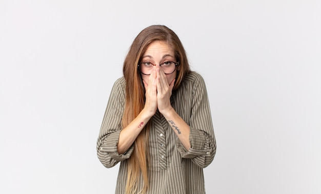 Femme assez mince se sentant inquiète, pleine d'espoir et religieuse, priant fidèlement avec les paumes pressées, implorant le pardon