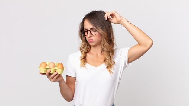 Femme assez mince se sentant perplexe et confuse, se grattant la tête et tenant une boîte à œufs