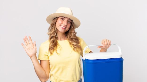 Femme assez mince souriant joyeusement, agitant la main, vous accueillant et vous saluant et tenant un réfrigérateur de pique-nique d'été