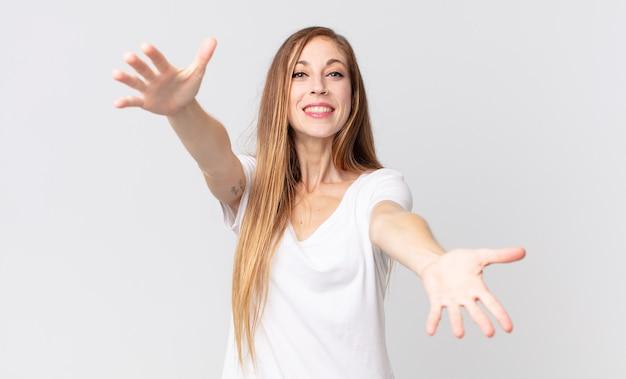Femme assez mince souriant joyeusement donnant un câlin de bienvenue chaleureux, amical et affectueux, se sentant heureuse et adorable