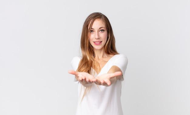 Femme assez mince souriant joyeusement avec un regard amical, confiant et positif, offrant et montrant un objet ou un concept