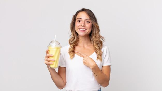 Femme assez mince souriant joyeusement, se sentant heureuse et pointant sur le côté et tenant un milk-shake à la vanille