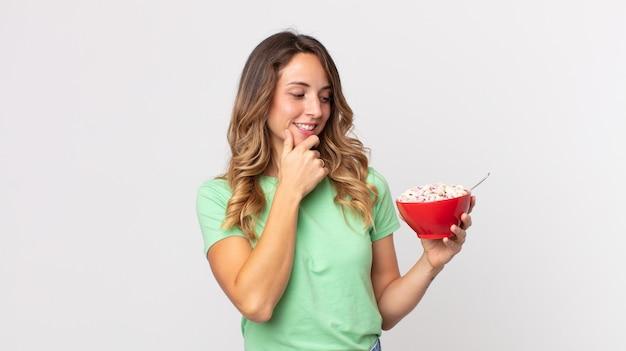 Femme assez mince souriante avec une expression heureuse et confiante avec la main sur le menton et tenant un bol de petit-déjeuner