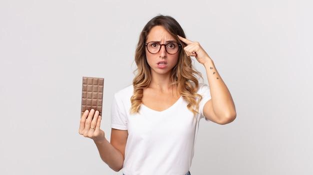 Femme assez mince à la surprise, réalisant une nouvelle pensée, idée ou concept et tenant une barre de chocolat