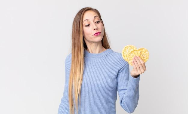 Femme assez mince tenant des gâteaux de régime de riz