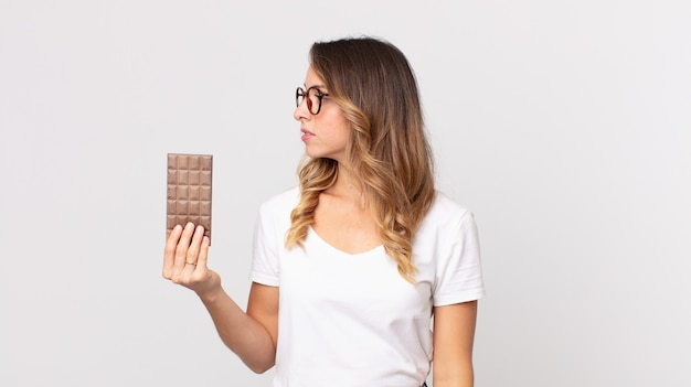 Femme assez mince sur la vue de profil pensant, imaginant ou rêvant et tenant une barre de chocolat