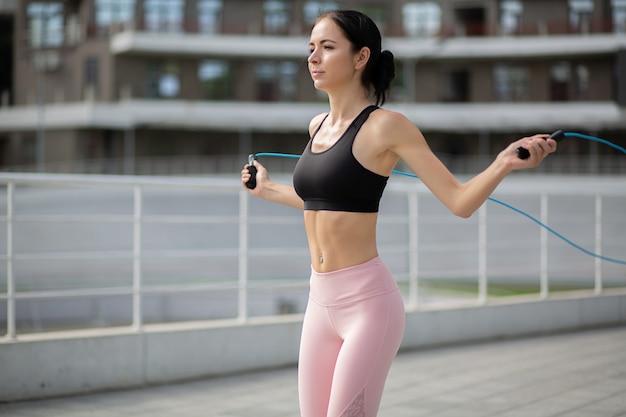Femme assez sportive sautant avec une corde à sauter au stade