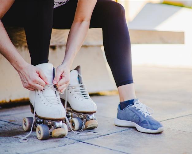 Femme, assis, attacher, patin à roulettes