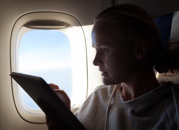 Femme, assis, par, illuminateur, dans, avion, à, tablette tactile