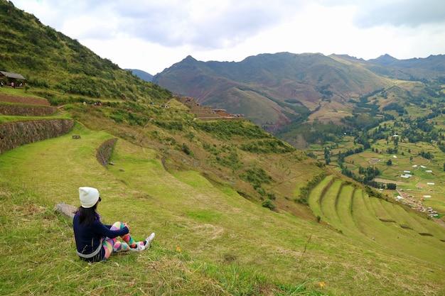 Femme assise sur les anciennes terrasses agricoles incas du site archéologique de pisac, cusco, pérou