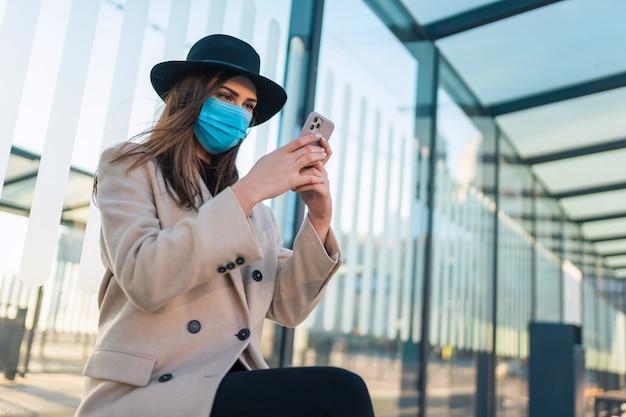 Femme assise à l'arrêt de bus pendant la pandémie