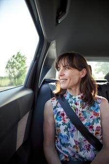 Femme assise à l'arrière d'une voiture