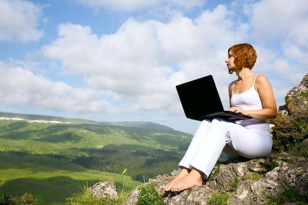 Femme assise au bord d'une falaise avec un ordinateur portable