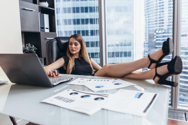 Femme assise au bureau avec des jambes sur une table travaillant sur un ordinateur portable analysant les statistiques financières de l'entreprise.
