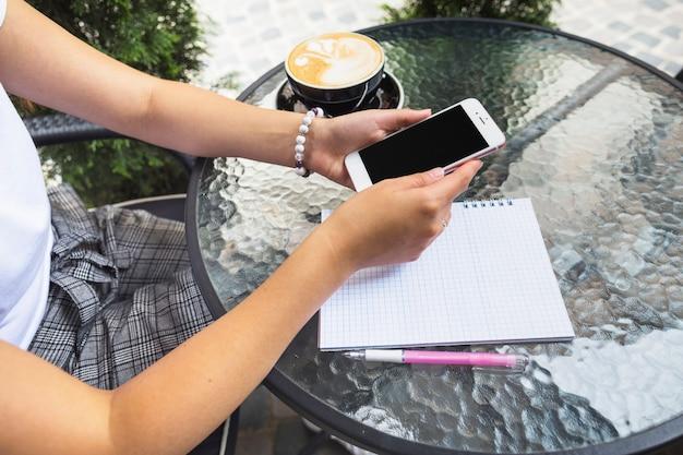 Femme assise au café en plein air à l'aide de téléphone portable