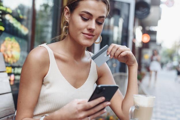 Femme assise au café tenant un téléphone portable et une carte de crédit
