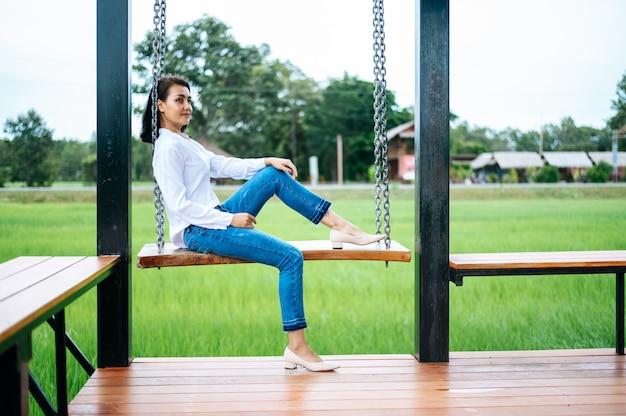 Femme assise sur la balançoire et posa ses mains sur ses genoux