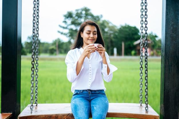 Femme assise sur une balançoire et tenant une tasse de café