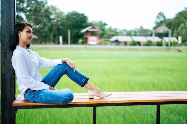 Femme assise sur un balcon en bois et posant ses mains sur ses genoux