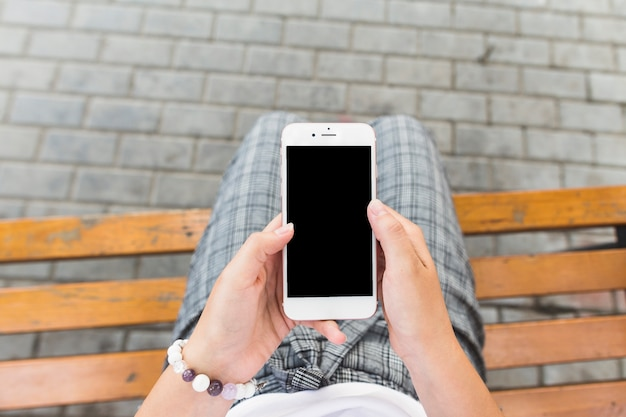 Femme assise sur un banc à l'aide de téléphone portable