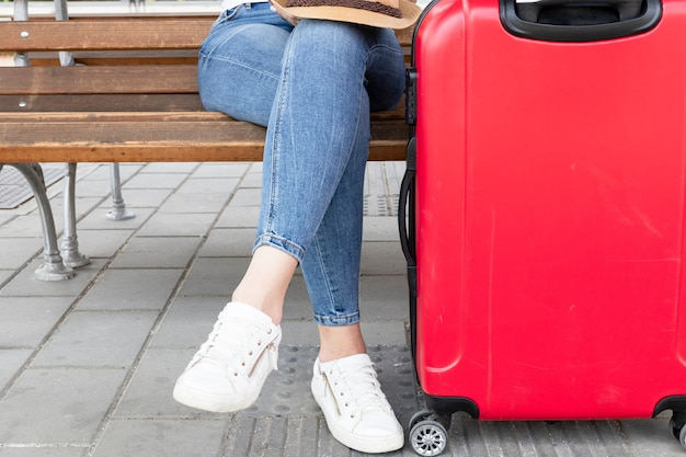Femme assise sur un banc avec un bagage