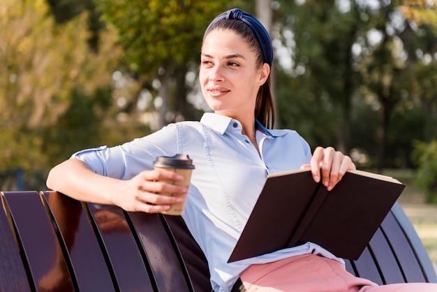 Femme assise sur un banc en bois, lisant un livre et buvant du café