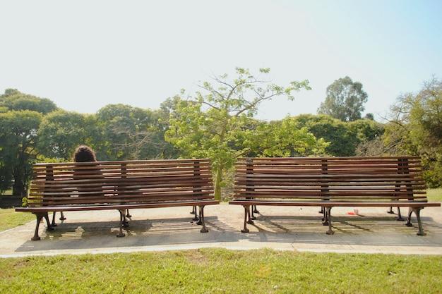 Femme assise sur un banc dans un parc naturel.