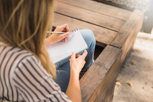 Femme assise sur un banc, écrivant sur un cahier avec un crayon
