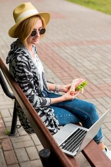 Femme assise sur un banc et mangeant