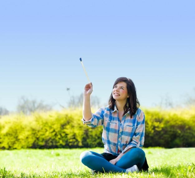 Femme assise avec un bâton