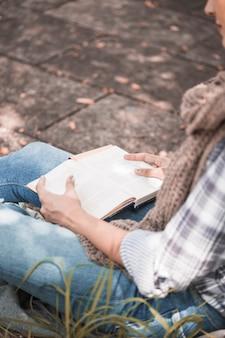 Femme assise à bord avec livre en journée ensoleillée