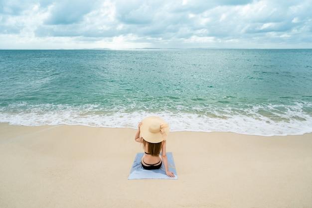 Femme assise sur le bord de la mer porter un bikini portant un chapeau de mer, l'environnement lumineux