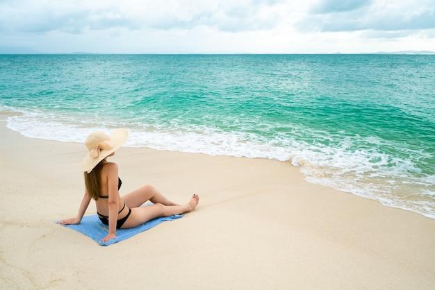 Femme assise sur le bord de la mer porter un bikini portant un chapeau de mer, l'environnement lumineux et c