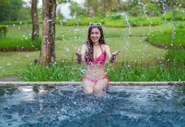 Femme assise sur le bord de la piscine et jouant des éclaboussures d'eau