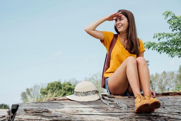 Femme assise sur une bûche et regardant ailleurs