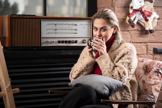 Une femme assise et buvant du café