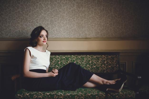 Femme assise sur un canapé antique